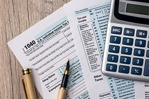 tax forms with calculator and pens